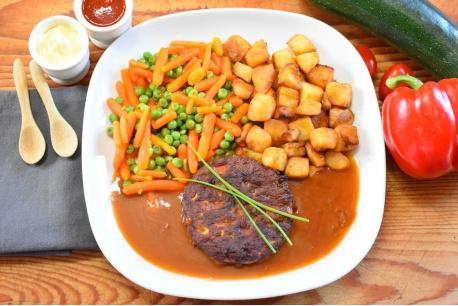 Groentenburger met worteltjes en doperwten en gebakken aardappeltjes